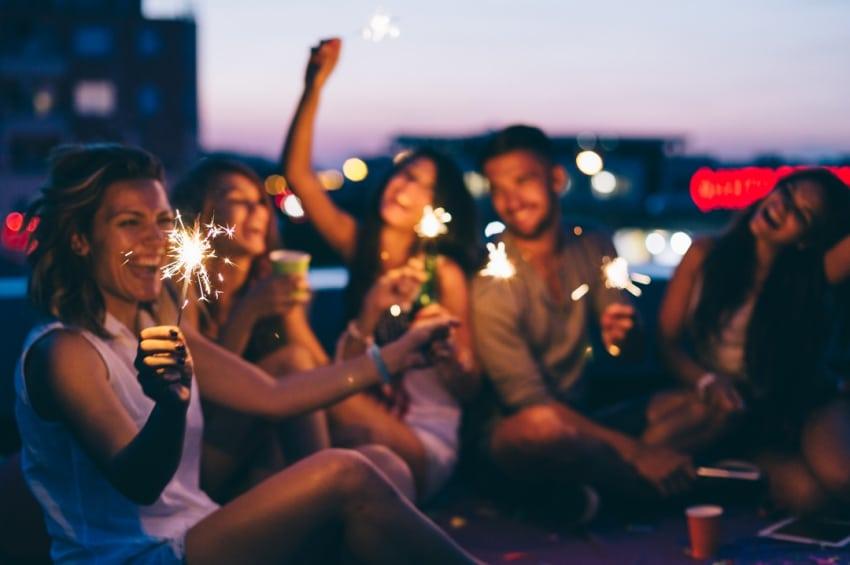 bande de jeunes qui fait la fete sur le toit dun immeuble avec des bieres et des bougies