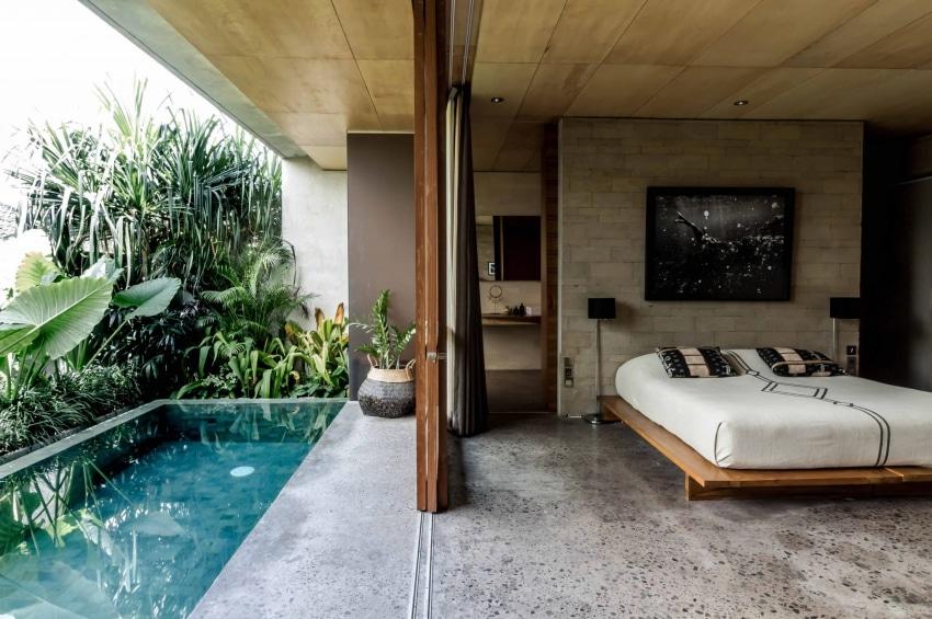 chambre dhotel avec piscine privative entouree de plantes et un grand lit en bois