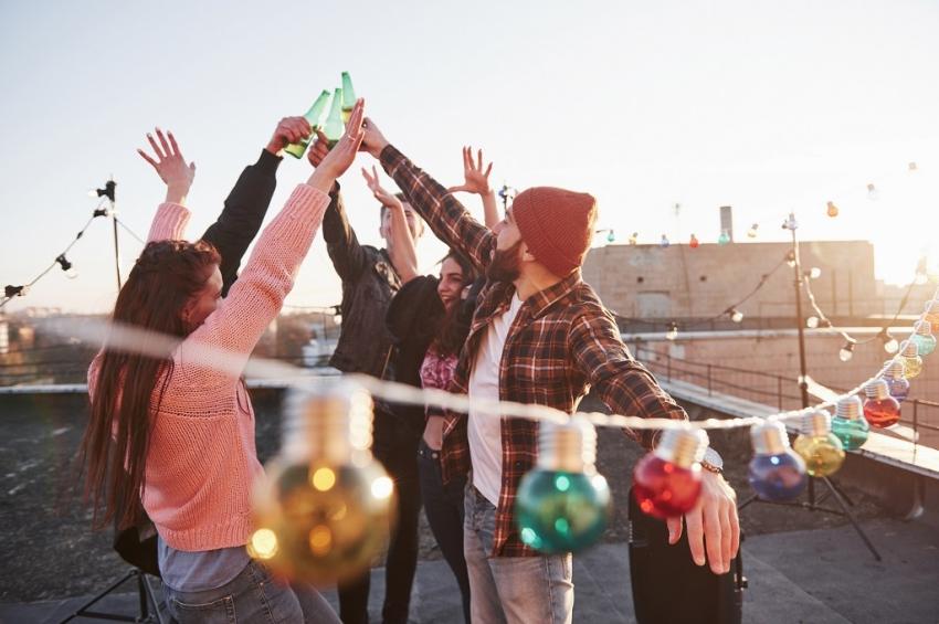 cinq amis qui font la fete sur un toit avec des guirlandes