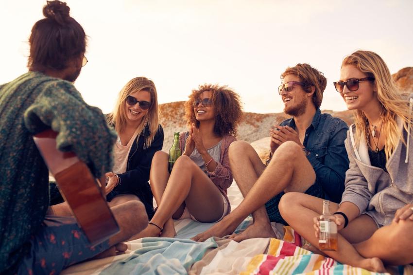cinq amis sur une plage qui boivent des bieres en jouant de la musique