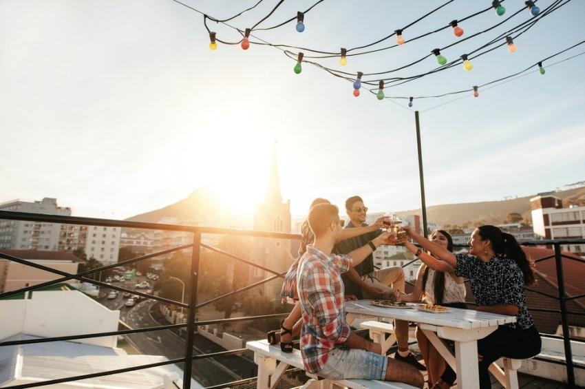 des amis qui trinquent en terrasse avec le soleil dans le dos