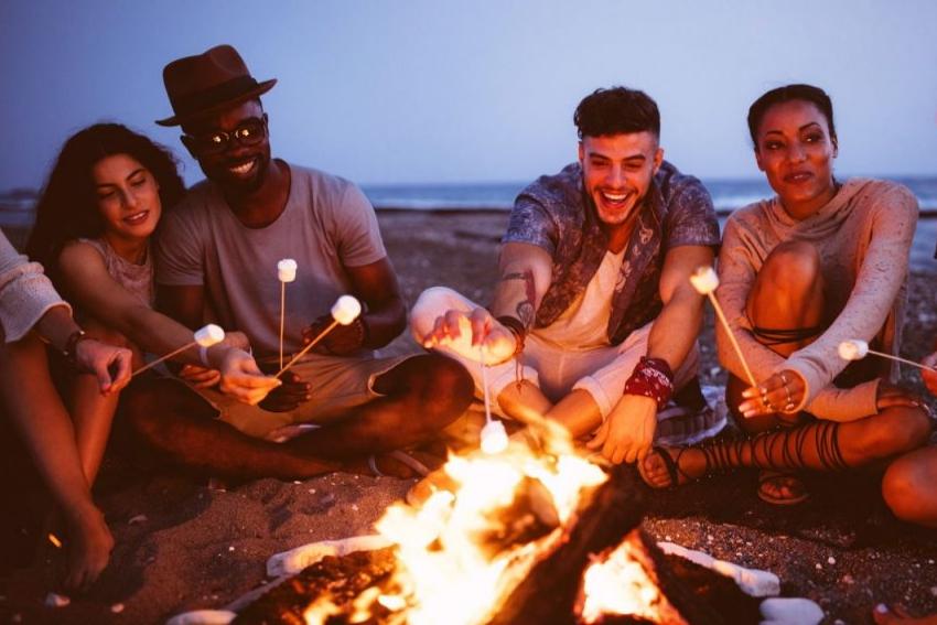 groupe damis autour dun feu sur la plage avec des chamallows