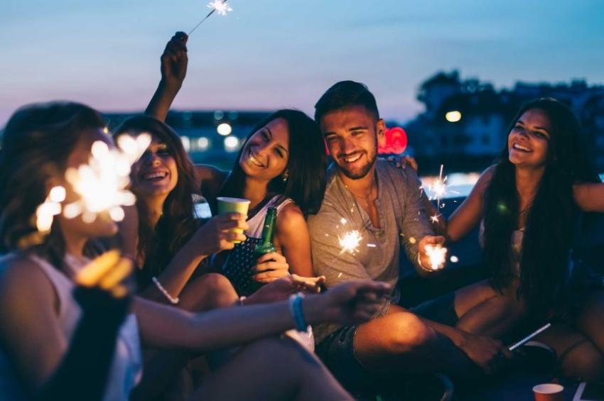 groupe damis buvant des verres avec des bougies feux dartifice sur le toit dun rooftop