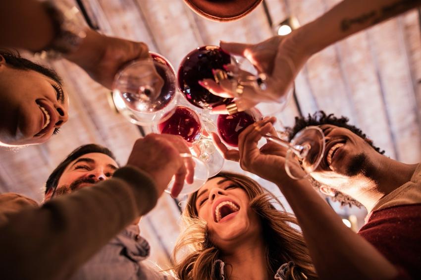 groupe d'amis buvant un verre de vin tout en rigolant