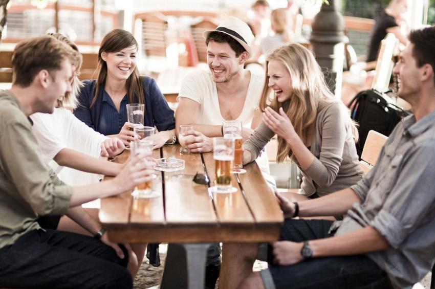 groupe damis qui boit des bieres en rigolant sur une terrasse