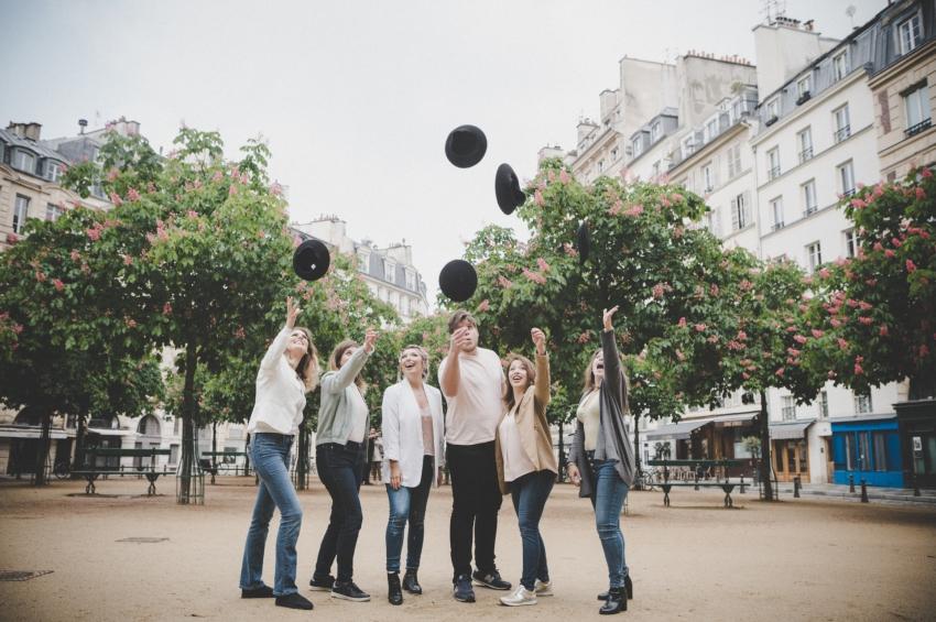 groupe damis sur une place parisienne qui lance des chapeaux dans les airs