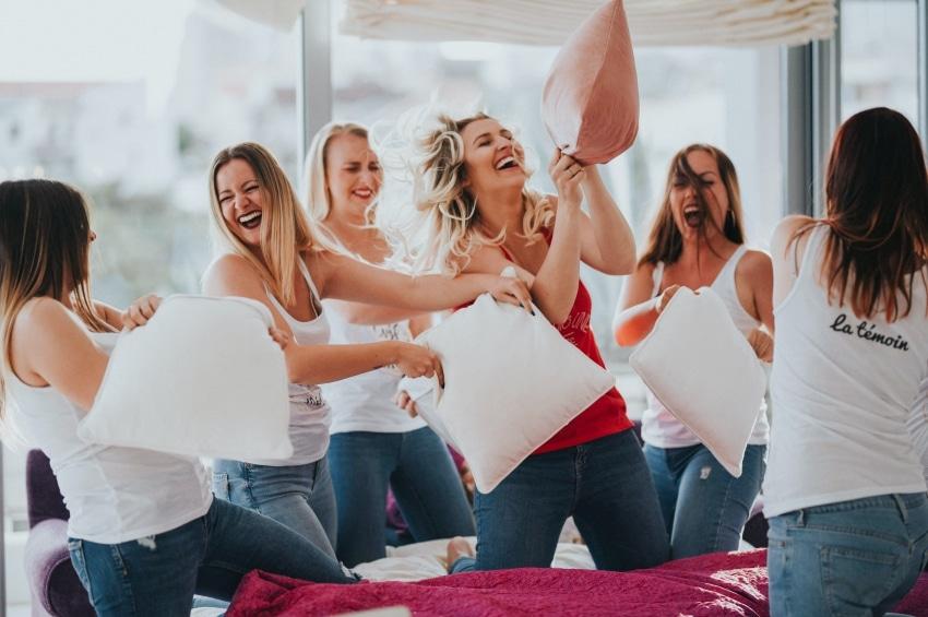 groupe de filles en train de faire une bataille de polochons dans une chambre dhotel