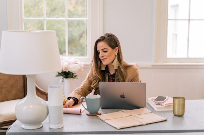 jeune femme travaille a son bureau avec une tasse de cafe et son ordinateur
