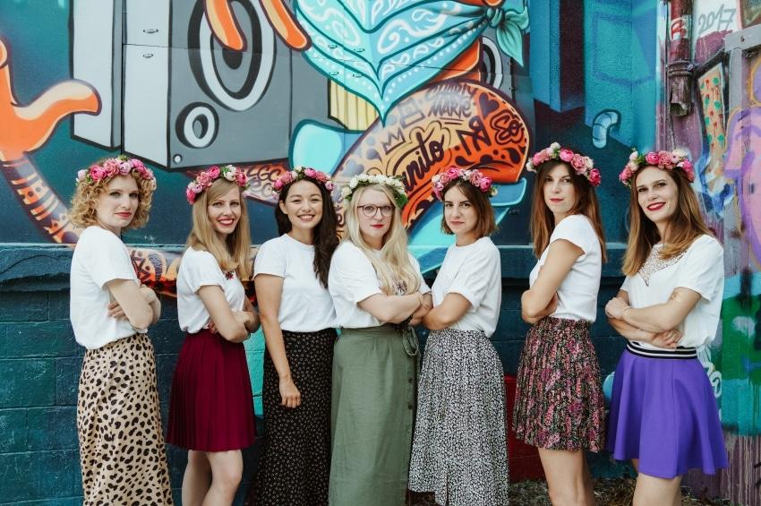 jeunes femmes avec couronne de fleur bras coirses devant des graffitis