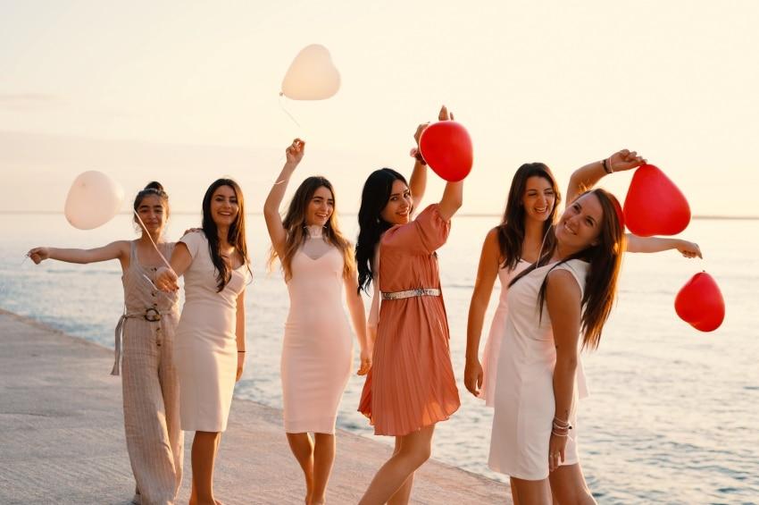 jeunes filles sur la plage avec des ballons en forme de coeur pour un shooting photo