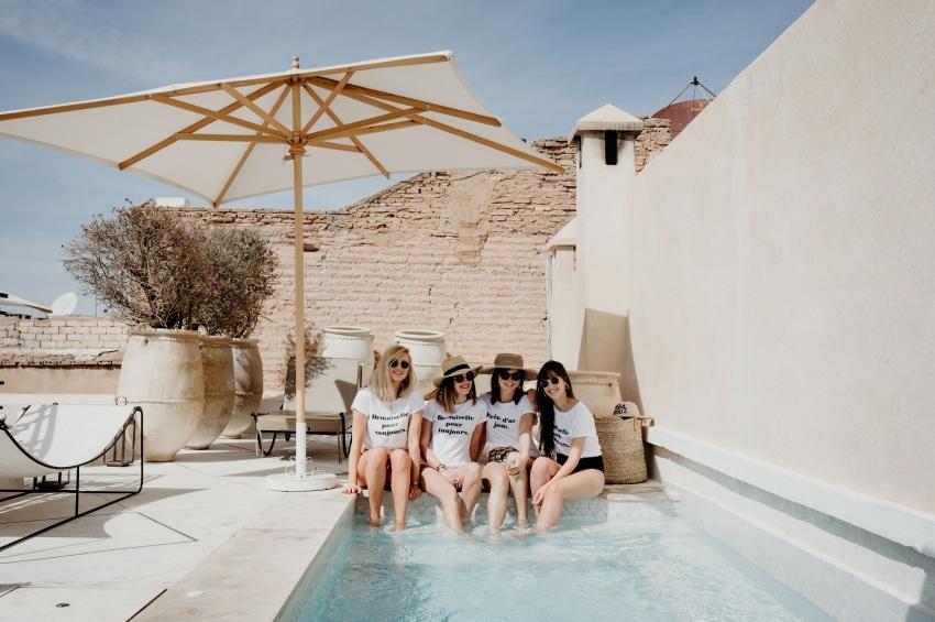 quatre filles assises les pieds dans leau au bord dune piscine sous un parasol