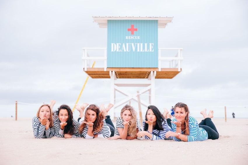 six filles couchees sur la plage de deauville pour un photoshoot devant la cabane de sauvetage