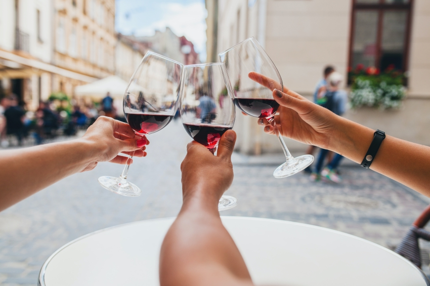 trois amis buvant un verre de vin sur une terrasse
