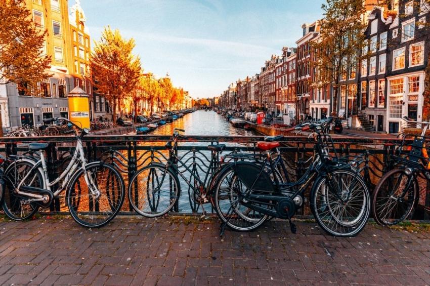 velos poses sur une barriere devant la riviere a amsterdam