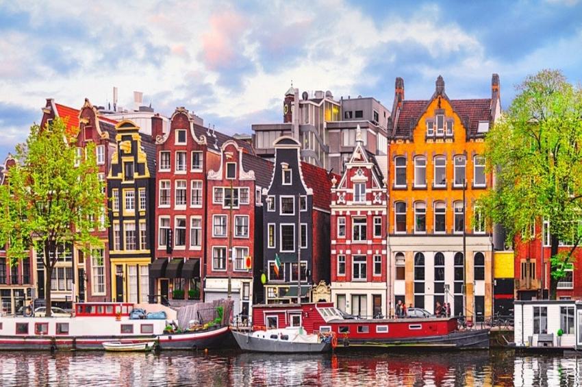 vue sur des maisons colorees et des bateaux sur le fleuve d'amstel a amsterdam
