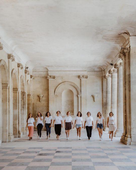 filles marchant en ligne sous un batiment avec des colonnes a bordeaux