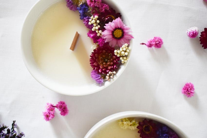 jolies bougies en fleurs sechees sur une table blanche