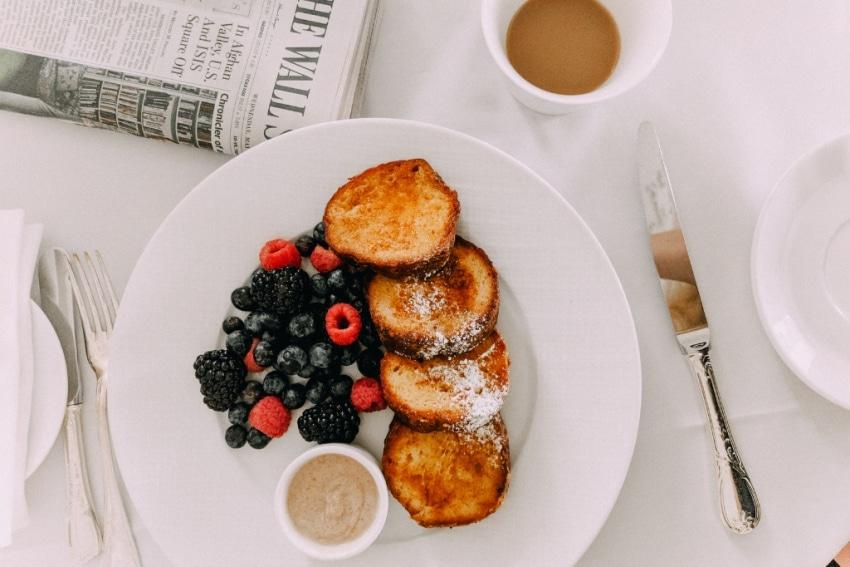 assiette blanche avec toasts et fruits rouges tasse de cafe au lait et journal