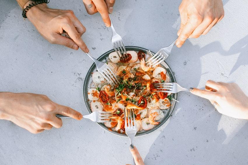assiette de crevettes et personnes qui mangent