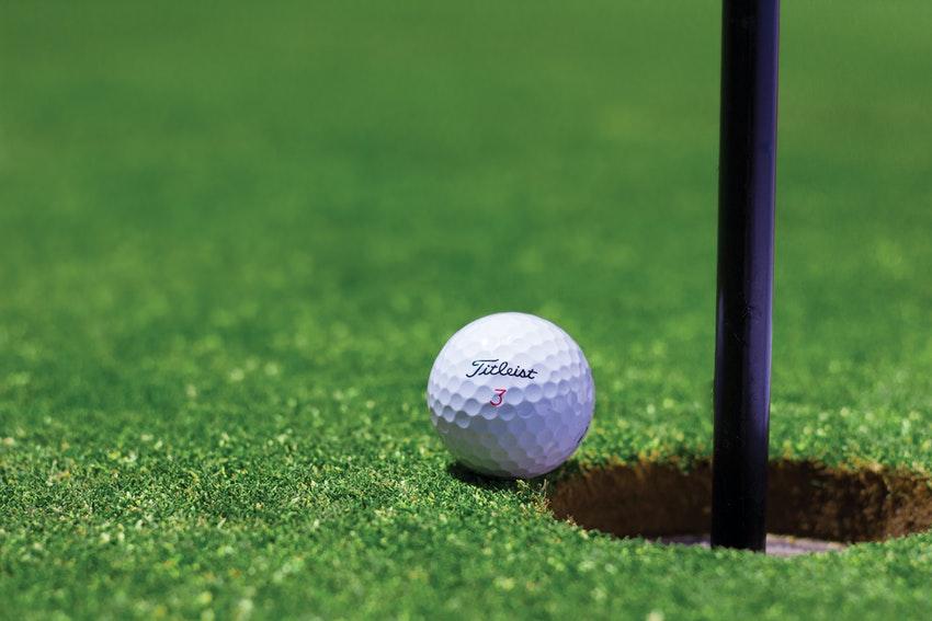balle de golf sur le green a cote du trou