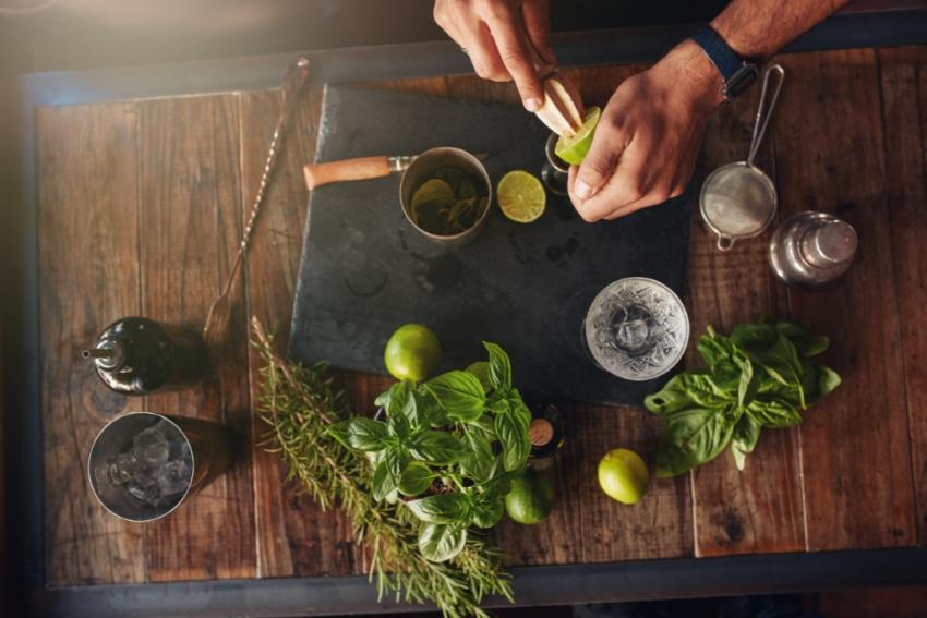 barman qui realise un mojito sur un plan de travail en bois avec bouquet de menthe et citron vert