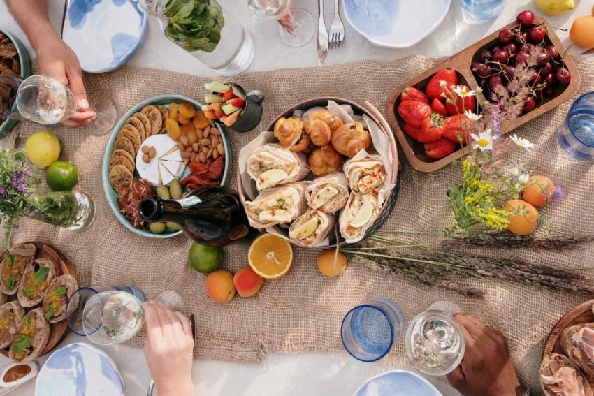 brunch sur une table avec chemin de table en toile de jute bouquet de fleurs bouteille de vin fruits legumes et viennoiseries