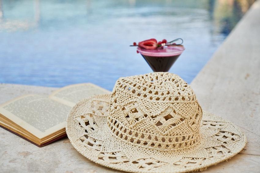 cocktail a la fraise au bord dune piscine avec un livre et un chapeau en macrame