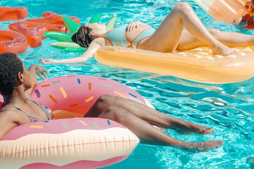deux femmes dans une piscine sur des bouees gonflables