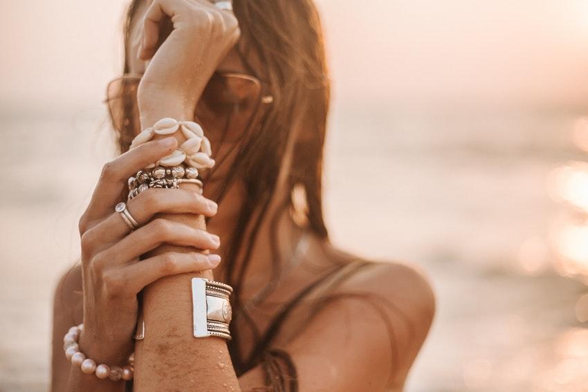 femme a la plage avec des bracelets sur le bras