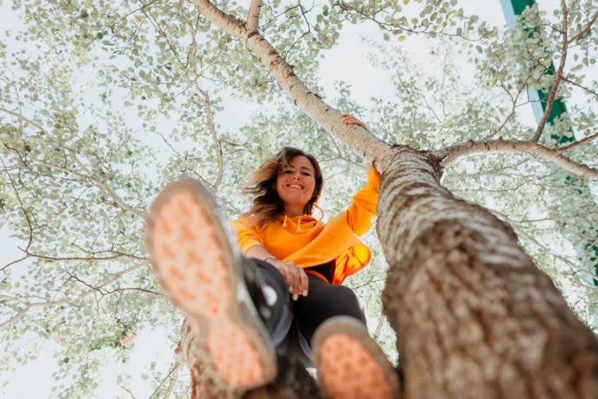 femme avec sweat orange et legging noir assise dans un arbre