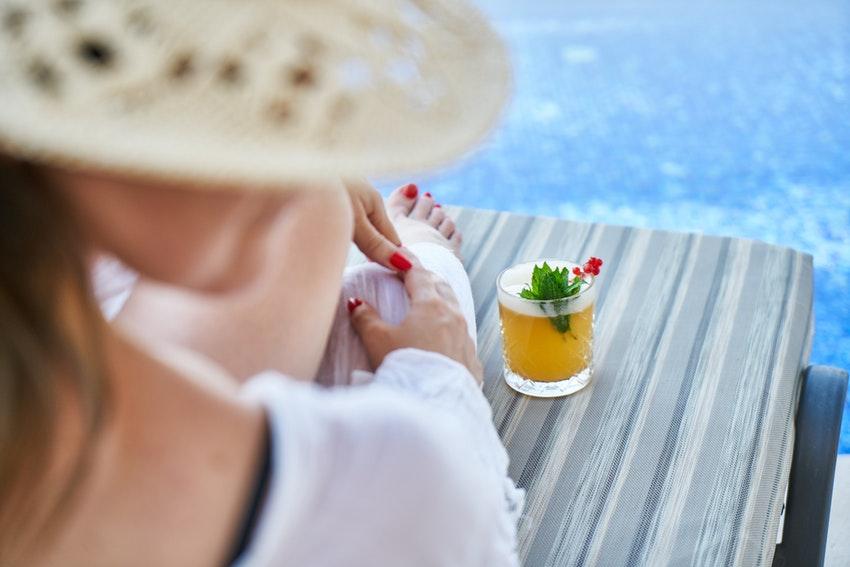 femme avec un chapeau allongee sur un transat entrain de boire un cocktail au bord de la piscine