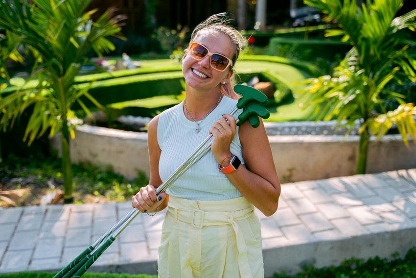 femme blonde avec lunettes de soleil qui porte des mini club de golf verts