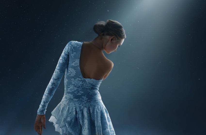 femme blonde en robe bleu de dos sous les projecteurs