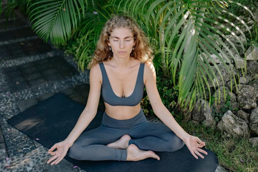 femme blonde en tenue de sport qui fait du yoga dans un parc