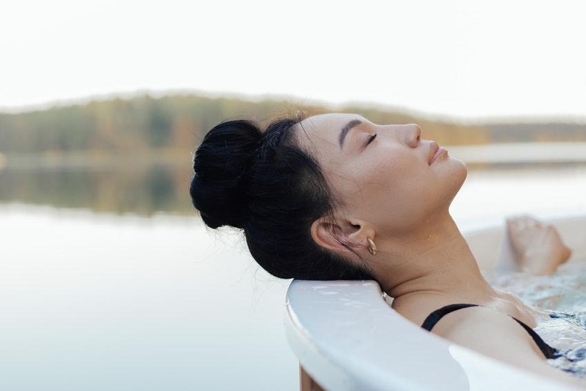 femme brune allongee dans un jacuzzi a la montage au bord dun lac