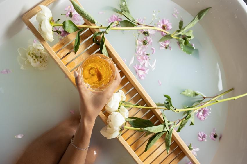 femme dans un bain qui tient un verre de champagne avec des fleurs dans leau