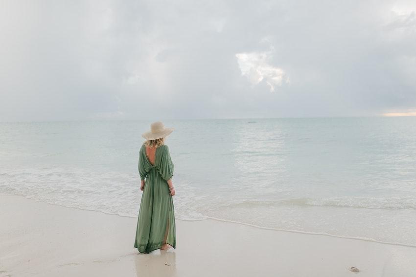 femme en robe longue verte avec un chapeau face a la mer