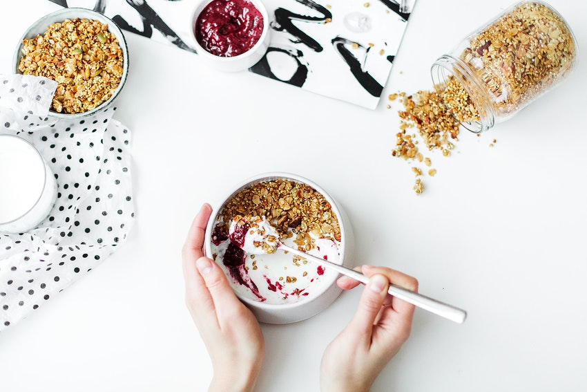 femme entrain de manger son petit déjeuner dans un bol avec du yaourt du granola et de la confiture