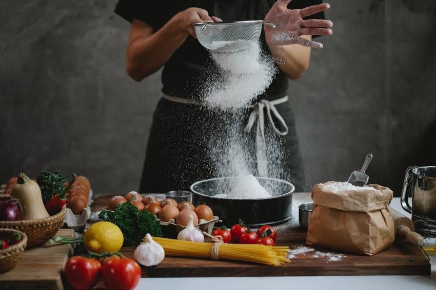 femme qui depose de la farine dans un plat sur un plan de travail rempli dingredients