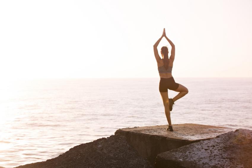 femme qui fait du yoga sur un rocher face a la mer