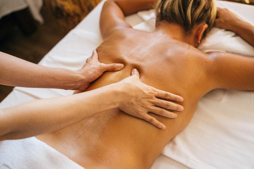femme sur le ventre qui se fait masser le dos
