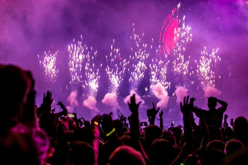 foule qui danse face a la scene avec lumiere et feu dartifice