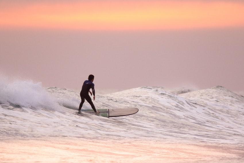 homme qui fait du surf au coucher de soleil