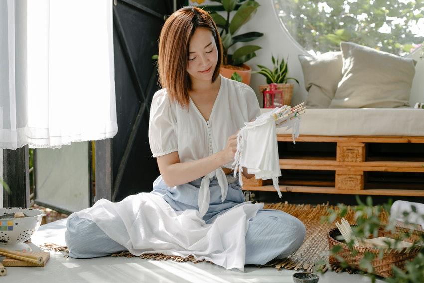 jeune femme asiatique assise par terre qui teint un vetement blanc
