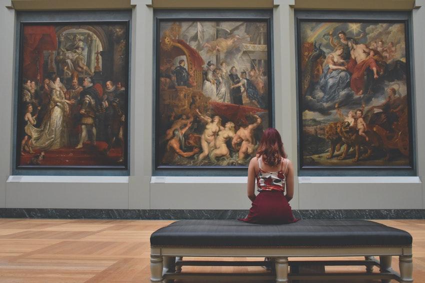 jeune femme assise sur un banc a linterieur dun musee qui observe des tableaux