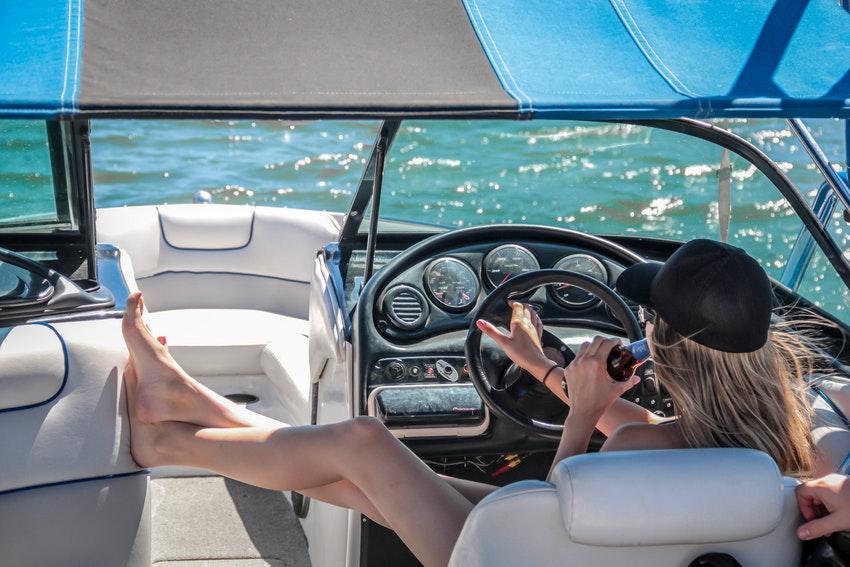 jeune femme au volant dun bateau en train de boire un coca
