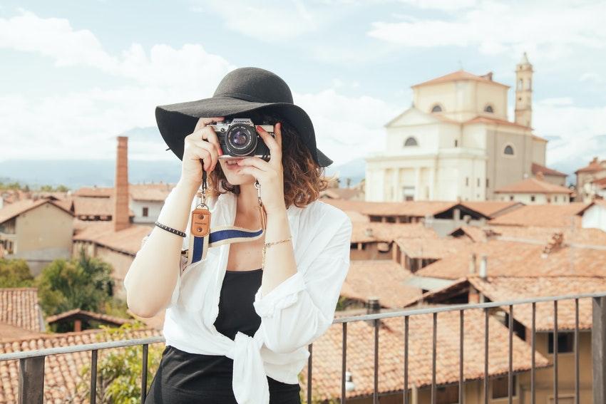 jeune femme avec un chapeau noir qui prend une photo en exterieur