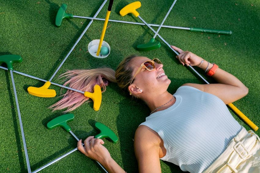 jeune femme blonde avec lunettes de soleil allongee sur le green avec des clubs de golf autour delle