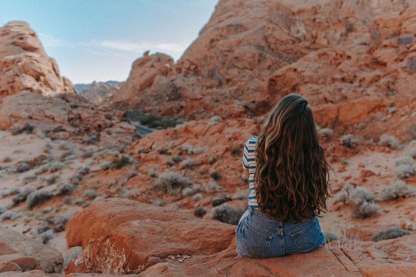 jeune femme brune avec tshirt a rayures assise sur une pierre