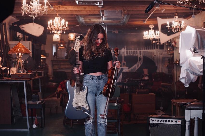 jeune femme dans un bar avec deux guitares electriques dans ses mains
